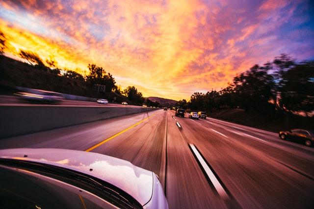 Kapota bieleho auta, ktorí de po ceste medzi ostatnými autami počas západu slnka.jpg