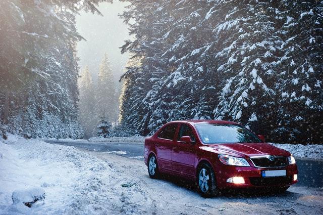 Červené auto stojí na zasneženej ceste.jpg