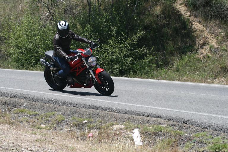 Jazdec na červenej motorke, asfalt, príroda